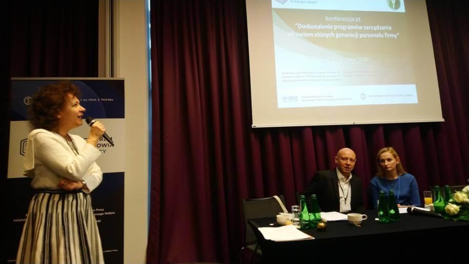 Zdjęcie zkonferencji, prelegent na scenie prowadzi wykład.